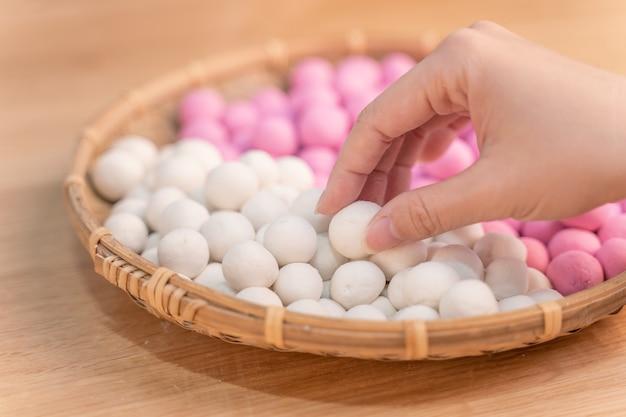Uma mulher asiática está fazendo tang yuan, yuan xiao, bolinhos de arroz com comida tradicional chinesa em vermelho e branco para o ano novo lunar, o festival de inverno, de perto.