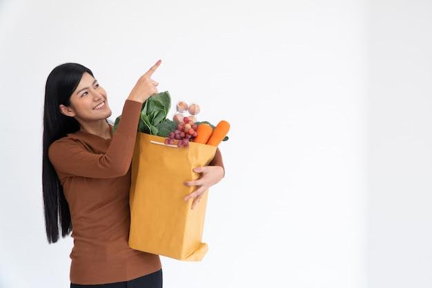 Uma mulher asiática feliz está sorrindo, com o dedo levantado e carregando uma sacola de papel de compras