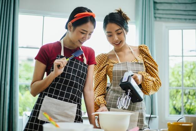 Uma mulher asiática jovem feliz no avental, sorrindo e cozinhando.