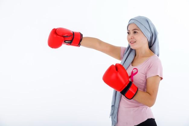 Uma mulher asiática lutando mostrando luvas de boxe no mês de conscientização do câncer de mama