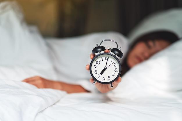 Uma mulher asiática segurando e mostrando um despertador enquanto dorme em uma cama aconchegante branca de manhã