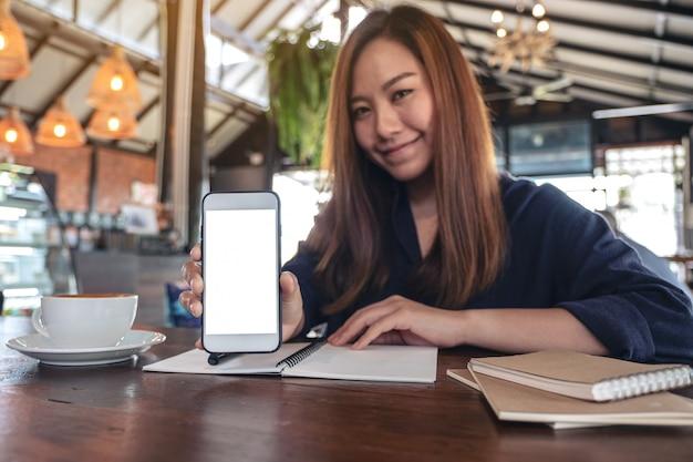 Uma mulher asiática segurando e mostrando um telefone celular branco com uma tela em branco com xícaras de café e cadernos em uma mesa de madeira vintage no café