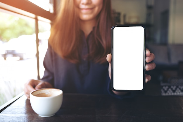 Uma mulher asiática segurando e mostrando um telefone celular preto com uma tela em branco e xícaras de café na mesa de madeira vintage