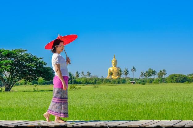 Uma mulher asiática segurando um guarda-chuva vermelho andando em uma ponte de madeira no campo de arroz com uma grande imagem dourada de buda.