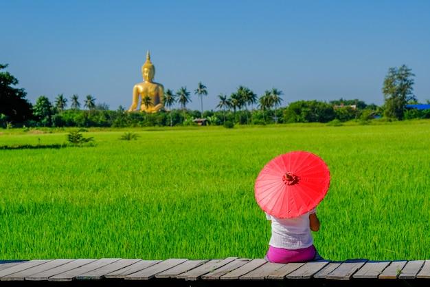 Uma mulher asiática segurando um guarda-chuva vermelho sentado em uma ponte de madeira em um campo de arroz com uma grande imagem dourada de buda.