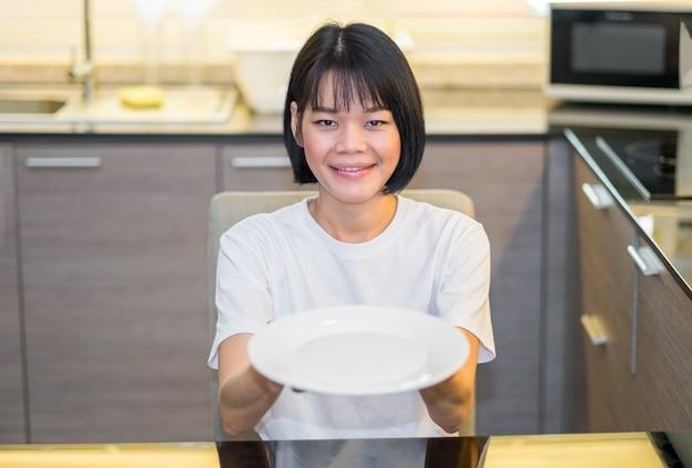 Uma mulher asiática segurando um prato branco vazio na cozinha de casa