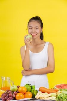 Uma mulher asiática segurando uma maçã verde com a mão direita e em cima da mesa há muitas frutas.