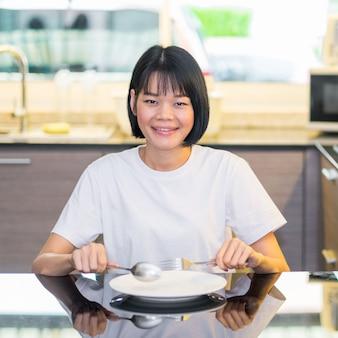 Uma mulher asiática sentada na cozinha com uma colher e um prato branco
