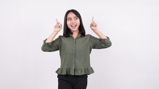 Uma mulher asiática sorridente apontando para cima contra uma parede branca