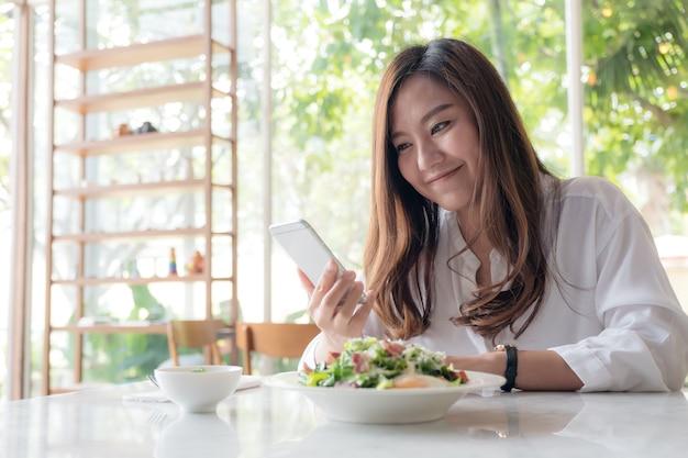 Uma mulher asiática usando e olhando para smartphone com salada em um prato branco na mesa