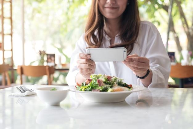 Uma mulher asiática usando smartphone para tirar foto de salada em um prato branco na mesa