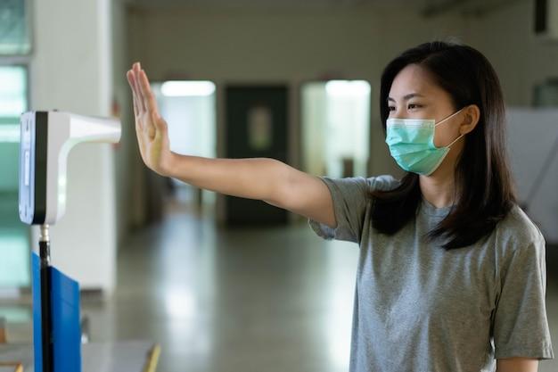 Uma mulher asiática usando uma máscara de óleo fica em pé para verificar a temperatura corporal do dia Foto Premium