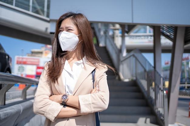 Uma mulher asiática usando uma máscara n95 vai trabalhar para evitar a poeira de pm2.5 no coração da cidade.