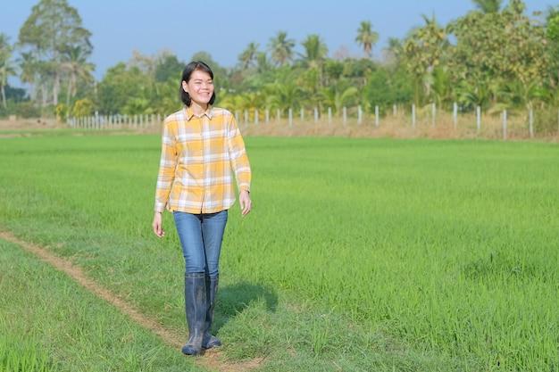 Uma mulher asiática vestindo uma camisa listrada amarela caminhava sorrindo alegremente no campo.