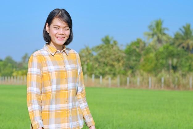 Uma mulher asiática, vestindo uma camisa listrada amarela, está sorrindo em um campo.