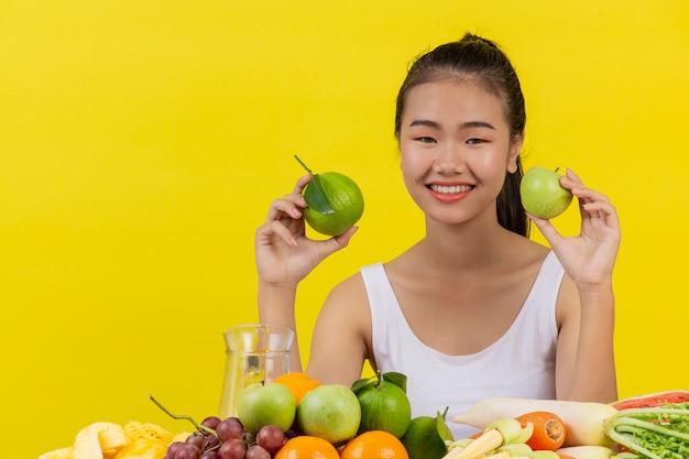 Uma mulher asiática vestindo uma camiseta branca. a mão esquerda segura a maçã, a mão direita segura uma laranja e a mesa está cheia de muitas frutas.