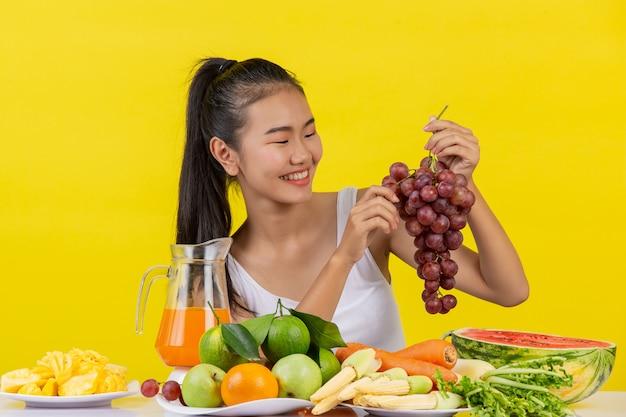 Uma mulher asiática vestindo uma camiseta branca. a mão esquerda segura um cacho de uvas. a mão direita pega as uvas para comer e a mesa está cheia de várias frutas.