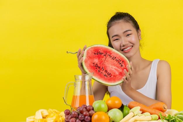 Uma mulher asiática vestindo uma camiseta branca. ambas as mãos seguram melancias e a mesa está cheia de várias frutas.