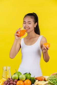 Uma mulher asiática vestindo uma camiseta branca. beber suco de laranja e em cima da mesa há muitas frutas.