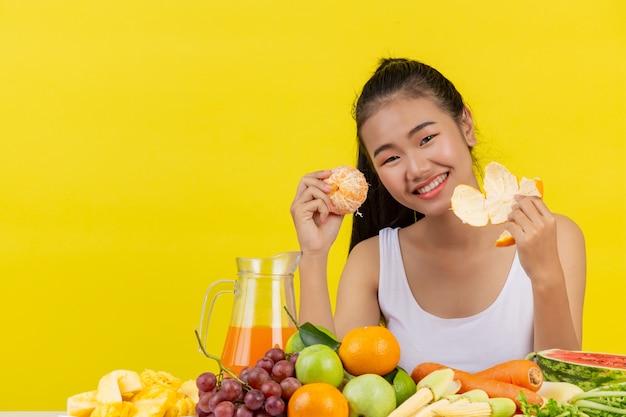 Uma mulher asiática vestindo uma camiseta branca. estou descascando ou descascando laranja e a mesa está cheia de vários tipos de frutas.