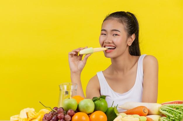 Uma mulher asiática vestindo uma camiseta branca. indo comer milho de bebê e na mesa há muitas frutas.