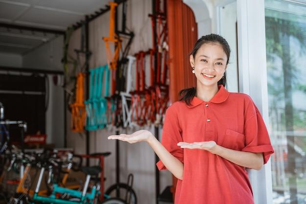 Uma mulher asiática vestindo uma camiseta de colarinho vermelho com um gesto de mão apresentando algo