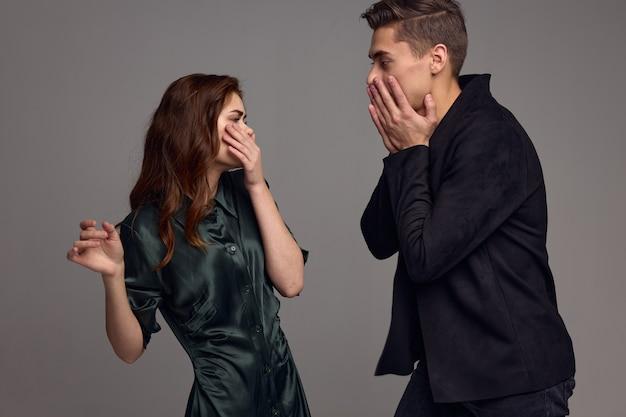 Uma mulher assustada e um homem surpreso se olham contra um fundo cinza. foto de alta qualidade