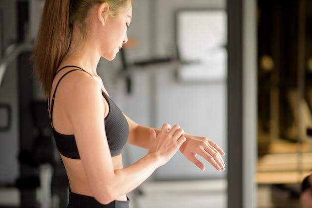 Uma mulher ativa está usando um relógio inteligente na academia