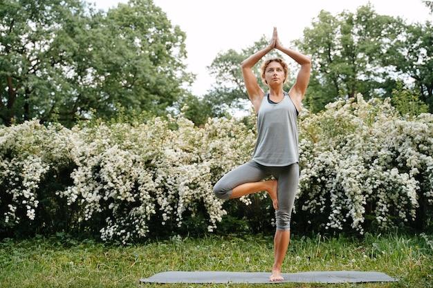 Uma mulher atlética e esguia em pose de árvore fazendo ioga em um conceito horizontal de parksports de verão e ampliando o espaço de cópia