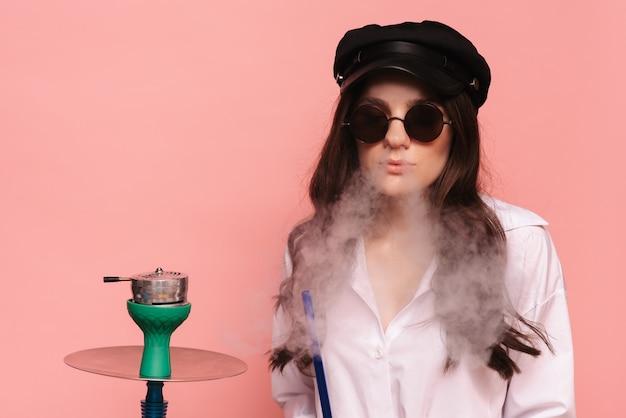 Uma mulher atraente de boné e óculos fuma narguilé e gosta de fumar