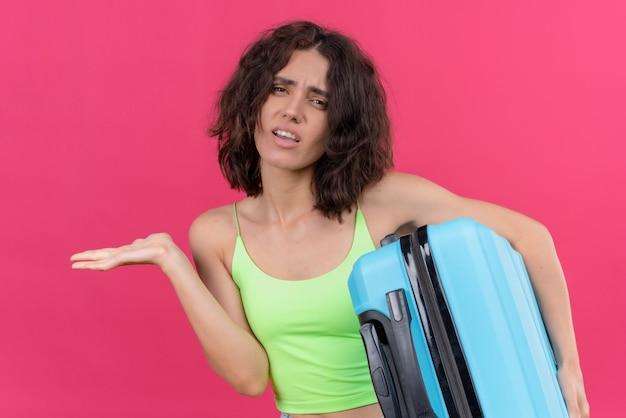 Uma mulher atraente e adorável com cabelo curto, vestindo uma blusa verde com as palmas das mãos abertas segurando uma mala azul