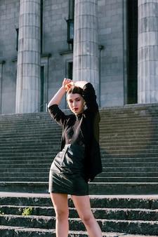 Uma mulher atraente em roupas da moda com as mãos na cabeça