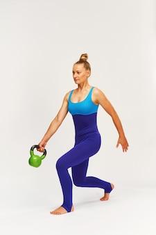 Uma mulher atraente em roupas esportivas, realiza exercícios de balanço com pesos