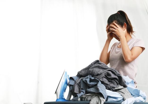 Uma mulher balança a cabeça estressada ao ver muitas roupas.
