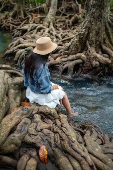 Uma mulher balançando os pés na água com a bela raiz de árvores em thapom klong song nam, krabi, tailândia.