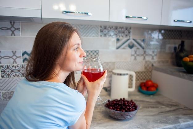 Uma mulher bebe vinho ou bebe sozinha na cozinha de casa. beber álcool sozinho