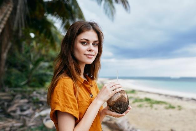 Uma mulher bebendo água de coco na praia com palmeiras