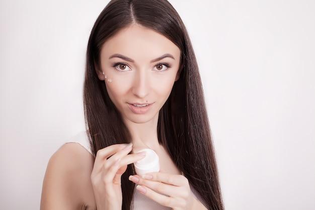 Uma mulher bonita ásia usando um produto de cuidados da pele, hidratante ou loção e skincare cuidando de sua pele seca. creme hidratante nas mãos femininas