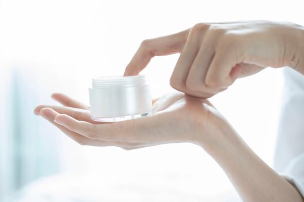 Uma mulher bonita asiática usando um produto de cuidados da pele, hidratante ou loção cuidando dele