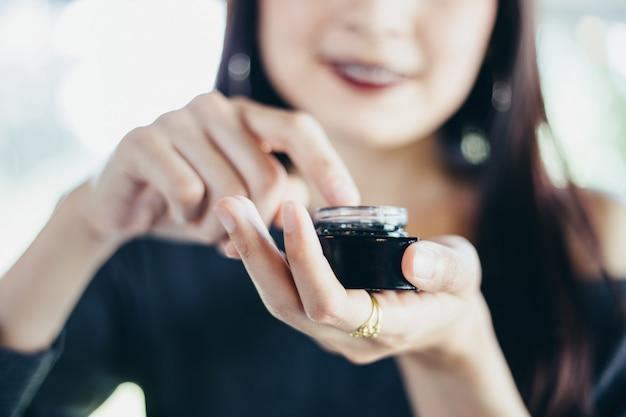 Uma mulher bonita asiática usando um produto de cuidados da pele, hidratante ou loção tomando cuidado