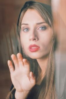 Uma mulher bonita atrás da janela