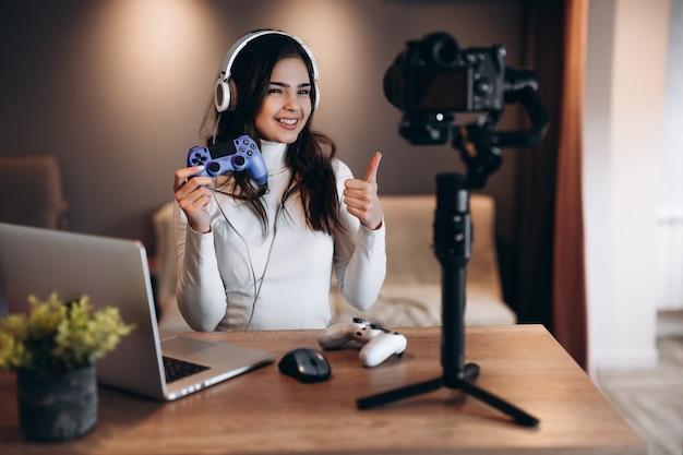 Uma mulher bonita blogueira com fones de ouvido está transmitindo ao vivo falando sobre videogames. jovem influente em transmissão ao vivo.