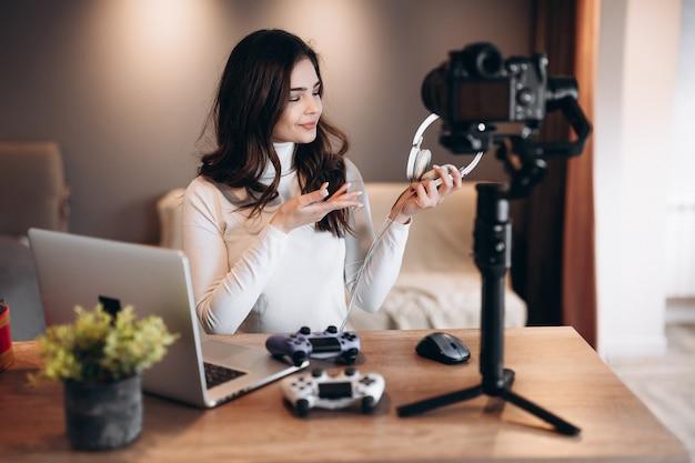 Uma mulher bonita blogueira está filmando e mostrando sua preferência em fones de ouvido para videogames. jovem influente em transmissão ao vivo.