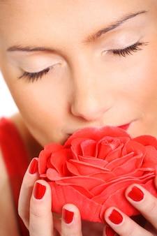 Uma mulher bonita cheirando uma rosa vermelha