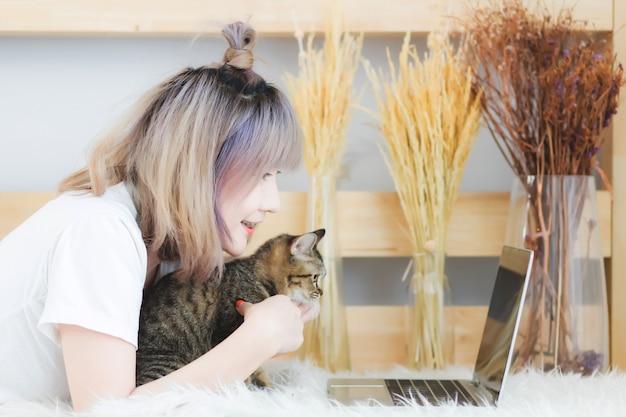 Uma mulher bonita com cabelo curto, o povo asiático, o povo tailandês usa roupas casuais, está deitado no cinema e um gato no tapete da sala de estar