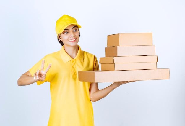 Uma mulher bonita com caixas de papel artesanal em branco marrom mostrando sinal de vitória.
