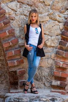 Uma mulher bonita, com longos cabelos loiros, blusa branca e calça azul na parede de pedra da cidade velha