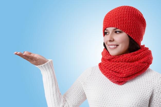Uma mulher bonita com sorriso agradável, vestindo roupas de inverno quente em pé lateralmente, levantando a mão e olhando de lado
