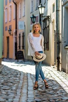 Uma mulher bonita com um chapéu claro, com longos cabelos loiros, uma blusa branca e jeans azul no meio da rua da cidade velha