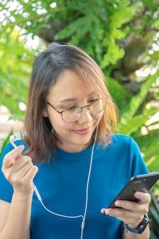 Uma mulher bonita com um smartphone diversão e sorridente mídia social digite mensagens de texto, converse com amigos,